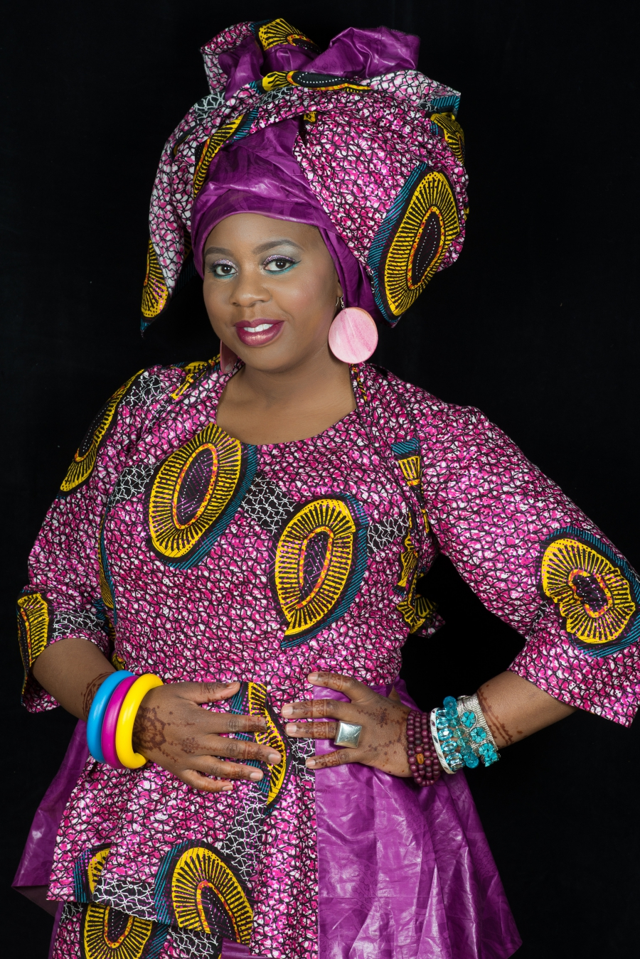 A woman is wearing a colorful pink dress and matching bright headwrap.
