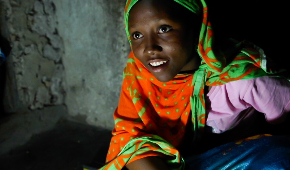"""Fourteen year-old Nuru Sheha studies at night in the light of solar-powered LED lights at home in the village of Matemwe, on the Tanzanian island of Zanzibar. He family's first electrical system was installed by one of Zanzibar's 13 """"solar mamas,"""" illiter"""