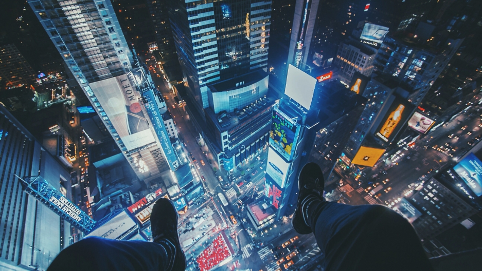 Humza Deas dangles his feet over Times Square.