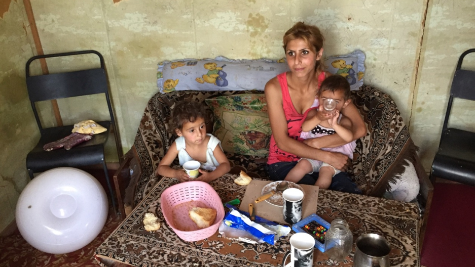 Melina fed her 2- and 3-year-old daughters in her domik in Armenia while her husband Artyom worked in Russia. He has since returned to be with his family but can't find work.