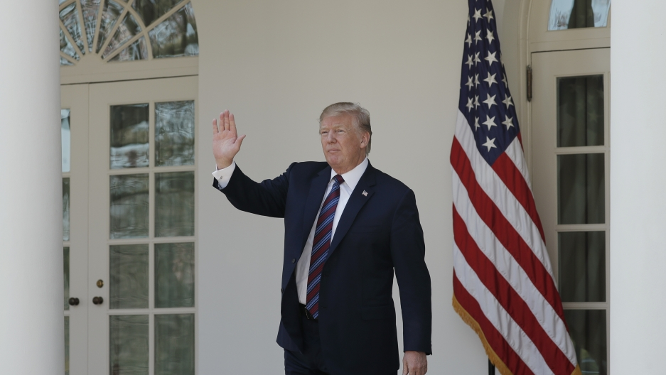 President Donald Trump, in a suit with the White House  behind him waves in the Rose Garden.