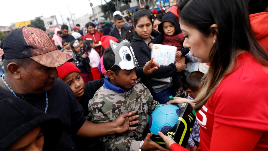 People hand out presents to children traveling with a caravan of migrants from Central America, near the San Ysidro checkpoint in Tijuana, Mexico April 30, 2018.