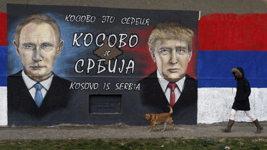 A woman passes by graffiti depicting the Russian President Vladimir Putin, left, and US President Elect Donald Trump in a suburb of Belgrade, Serbia