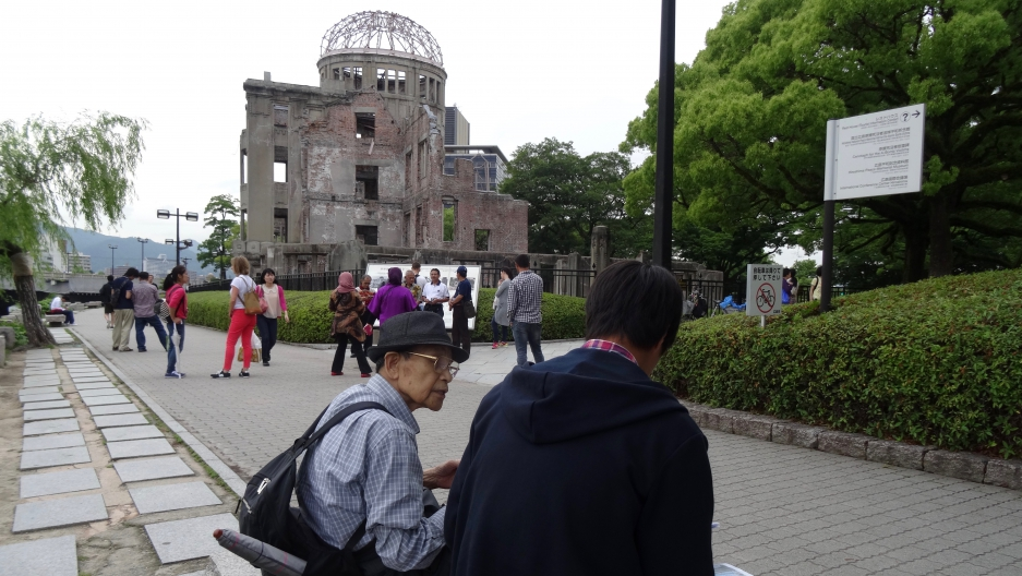 Hiroshima survivor Noriho Azuma (wearing a hat) in front of the A-bomb dome in June of 2015.