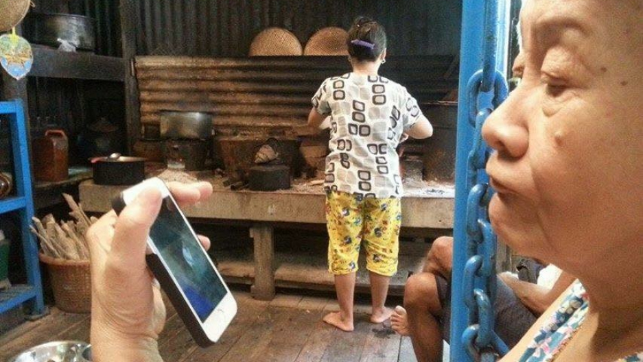 Burmese woman tries out her new cell phone