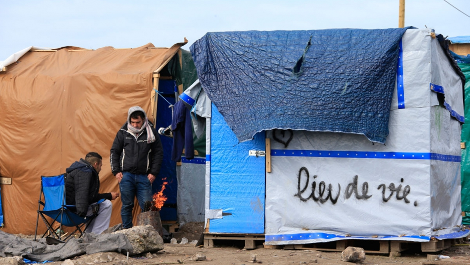 """Migrants get warm near a fire outside a makeshift shelter with the message, """"Place of Life."""""""