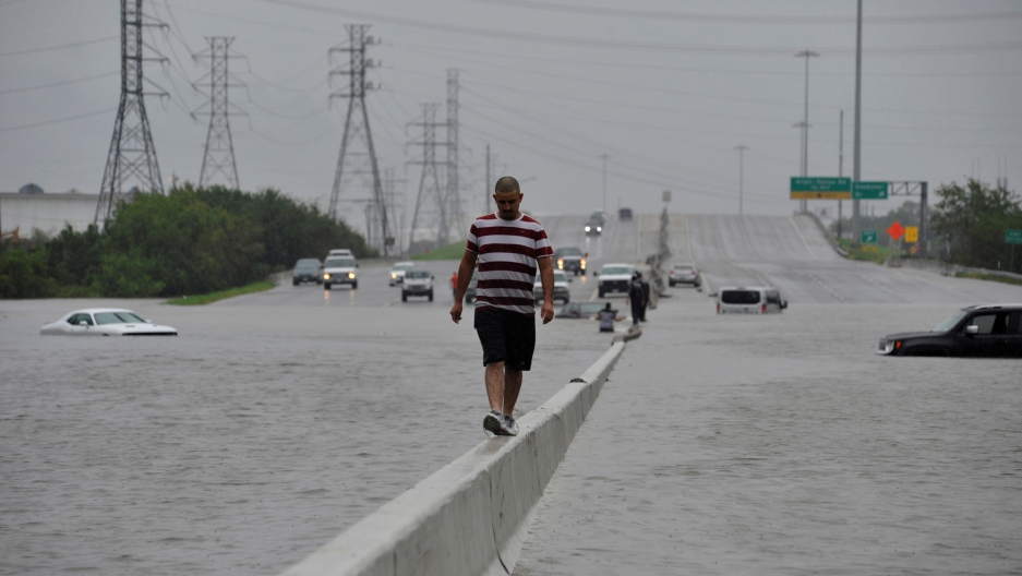 A stranded motorist escapes floodwaters on Interstate 225 after Hurricane Harvey inundated the Texas Gulf coast with rain causing mass flooding in Houston.