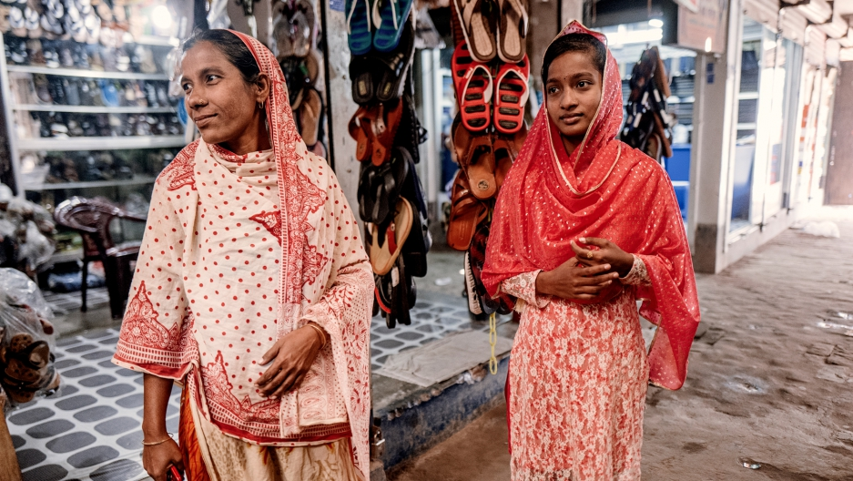 Rongmala Begum (L) and her 16-year-old daughter Mayna both work a the same garment factory making sweaters.