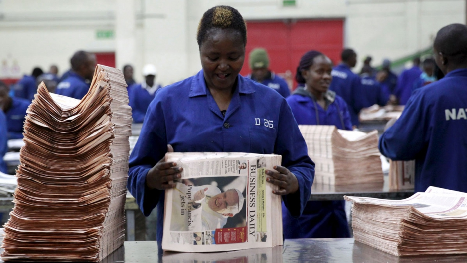 A worker arranges a copy of the Business Daily newspaper at a printing press plant on the outskirts of Nairobi.