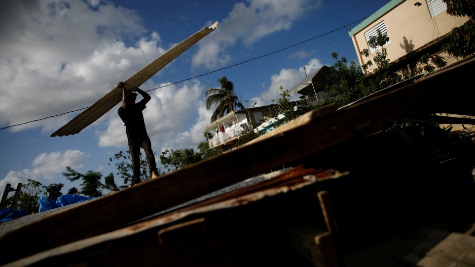 Carlos Ventura carries a corrugated metal sheet to be used for a ceiling, while he helps a neighbor to rebuild her house, which was partially destroyed by Hurricane Maria in Puerto Rico.