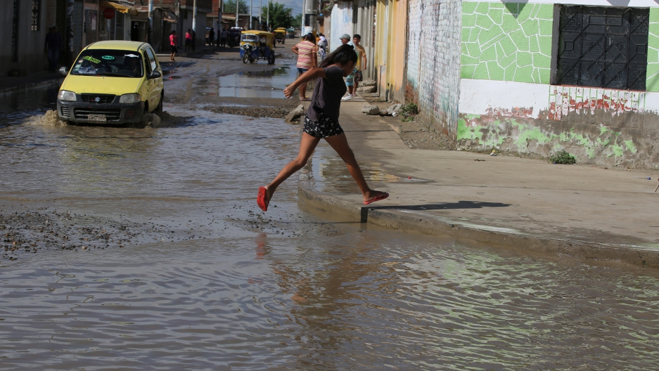 Woman crosses a flooded street in Piura, Peru.