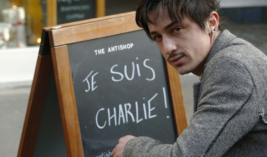 Adel Defilaux, a French-born Muslim, poses Wednesday outside his cafe in east London. Defilaux has received death threats for displaying the sign.