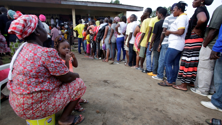 People wait to vote during the presidential election at a polling station of Duport Road in Monrovia, Liberia, Oct. 10, 2017.