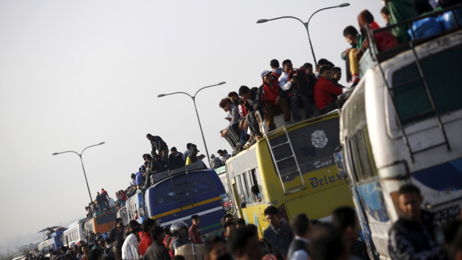Passengers ride inside and atop overcrowded buses as they head toward their village to celebrate a Hindu festival in Nepal in October 2015.