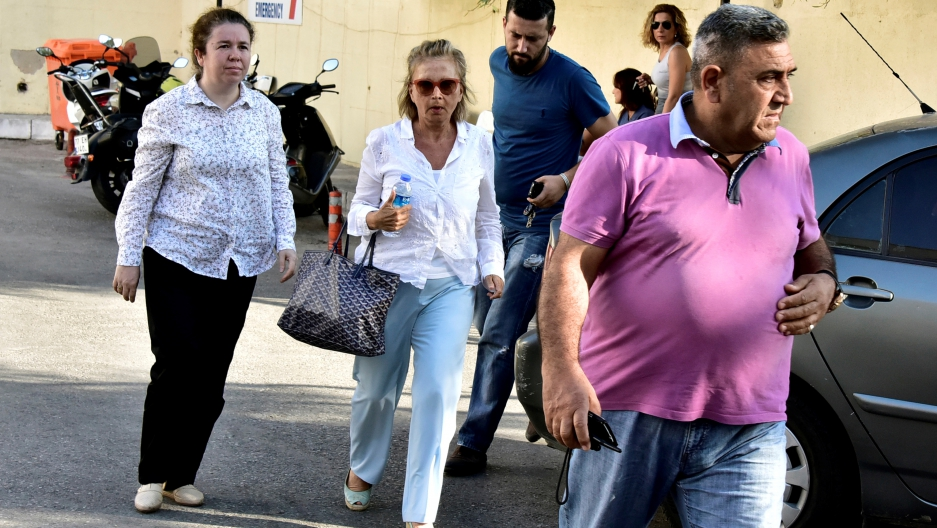Turkish journalist Nazli Ilicak (C), also a well-known commentator and former parliamentarian, is escorted by a police officer (R) and her relatives (L and rear) after being detained and brought to a hospital for a medical check in Bodrum, Turkey, July 26