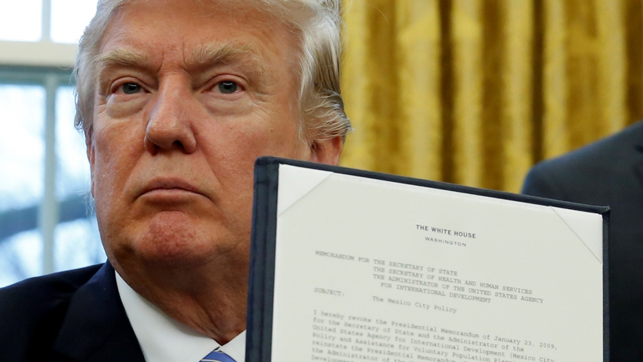 U.S. President Donald Trump holds up his executive order on the reinstatement of the Mexico City Policy.