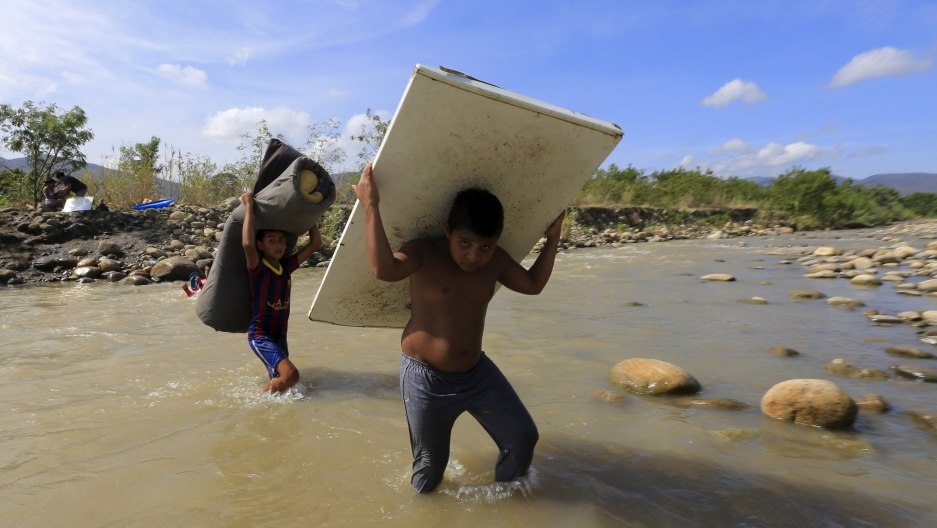 Boys carry their belongings as they cross the Tachira river border into Colombia from Venezuela, near Colombia's Villa del Rosario village, August 27, 2015.