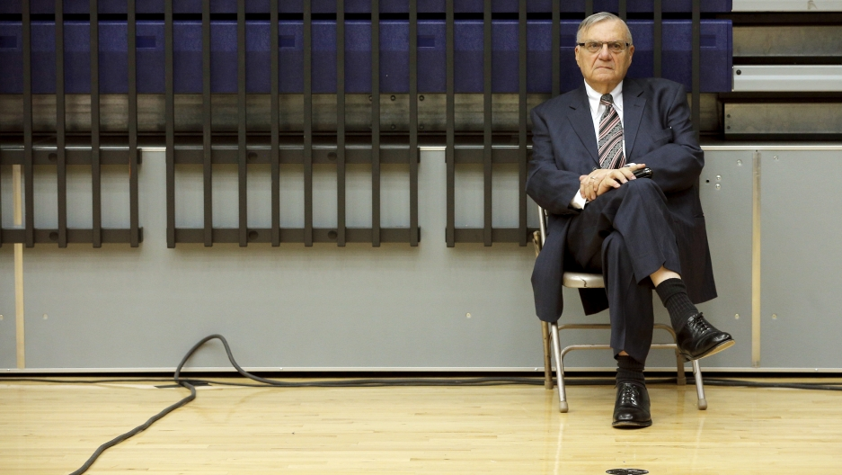 Arpaio sits on a folding chair in a gym