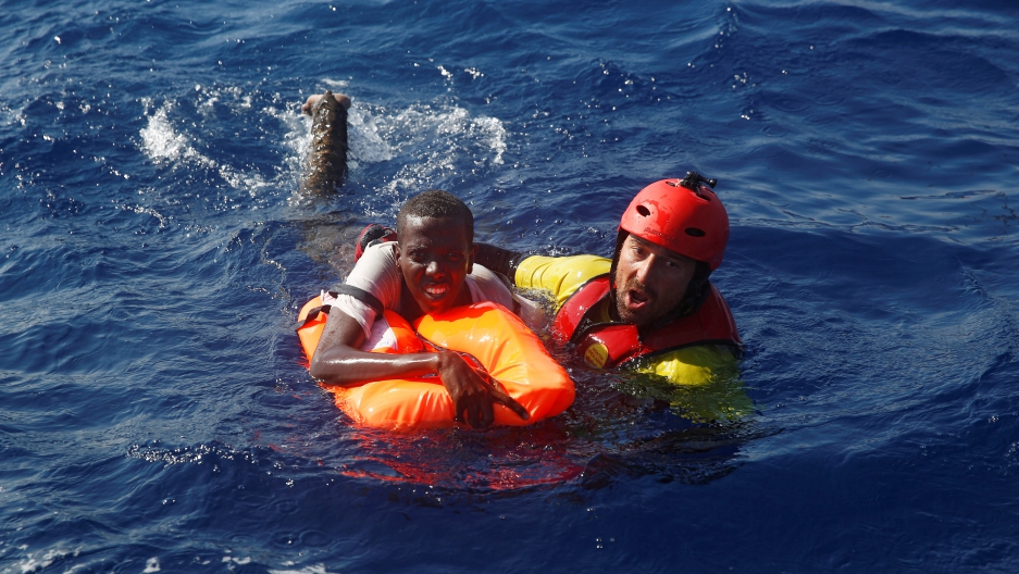 A member of the Spanish NGO Proactiva rescues a Somali migrant that fell from an overcrowded dinghy, during a rescue operation off the Libyan coast in Mediterranean Sea August 28 , 2016. REUTERS/Giorgos Moutafis
