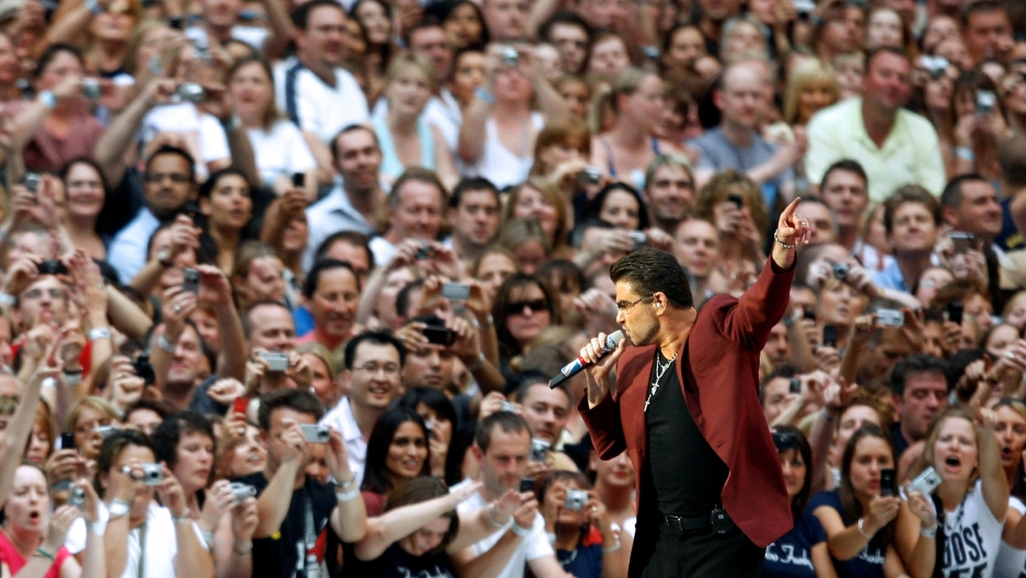 George Michael with a microphone in front of a crowd