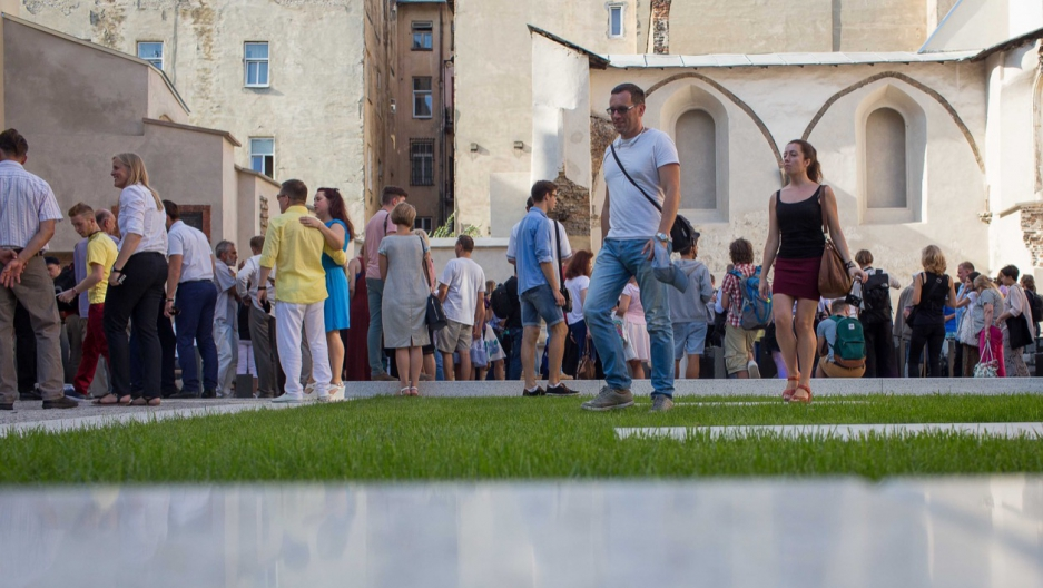 Visitors pass through an open space of grass and polished stone on the former site of the Beth Hamidrash, the study hall adjacent to the Golden Rose synagogue, in Lviv, Ukraine.