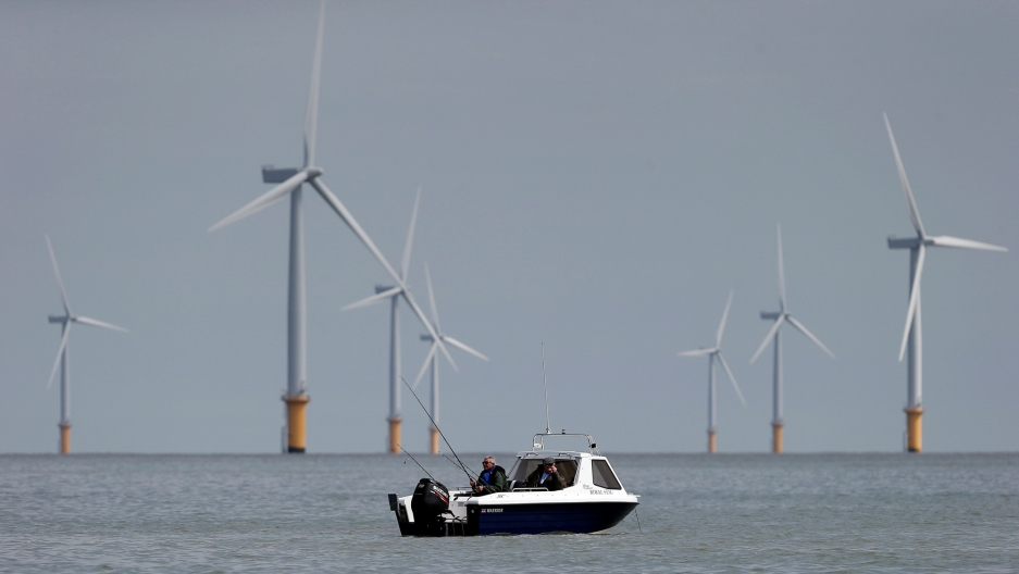 Two fishermen sit in their boat at the Gunfleet Sands Offshore Wind Farm near Clacton-on-Sea, Britain.