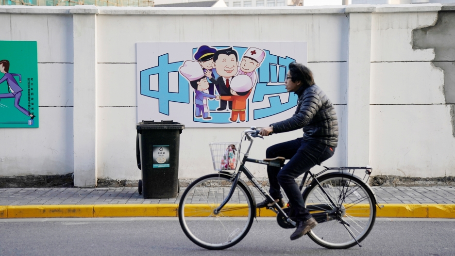 """A cartoon depicting Chinese President Xi Jinping with the Chinese characters reading """"Dream of China"""" is seen in the background as a bicyclist rides past."""