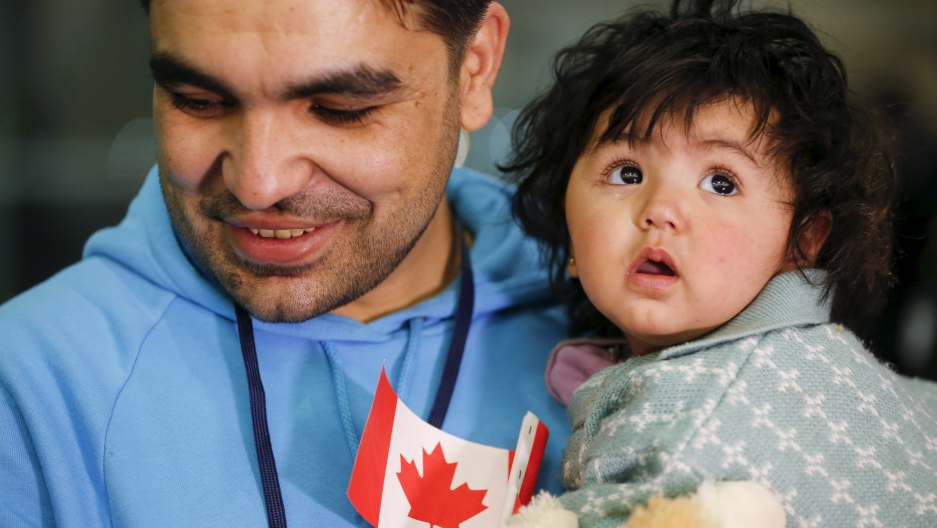 A Syrian refugee holds his daughter as they arrive at the Pearson Toronto International Airport in Mississauga, Ontario, December 18, 2015.