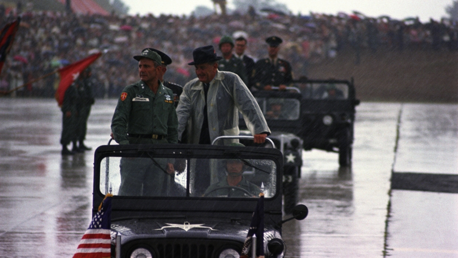Standing in a jeep during a rainstorm (L-R:) Maj. Gen. Ben Sternberg, Pres. Lyndon B. Johnson