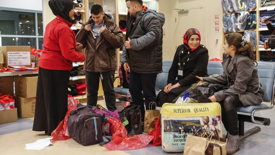 Syrian refugees receive winter clothing as they arrive at the Pearson Toronto International Airport in Mississauga, Ontario, December 18, 2015.