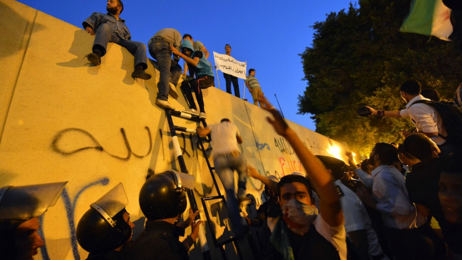 In Egypt, angry protesters scale US embassy walls, tear down