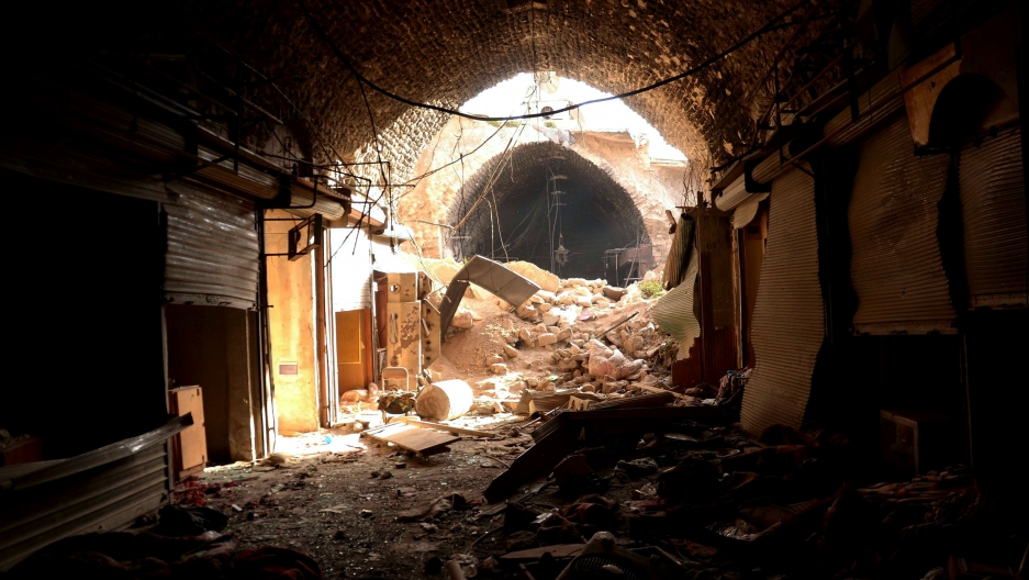 Rubble fills a tunnel that was a souk shop. Some shop locations are visible, with metal doors pulled down. There are no people, no lights.