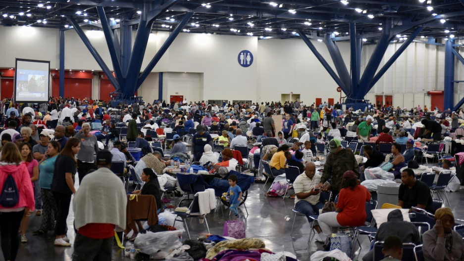 Hundreds of people are gathered in a room. Some are seated at tables and have water bottles, some pillow or blankets with them. A large screen is set up to broadcast news about Tropical Storm Harvey.