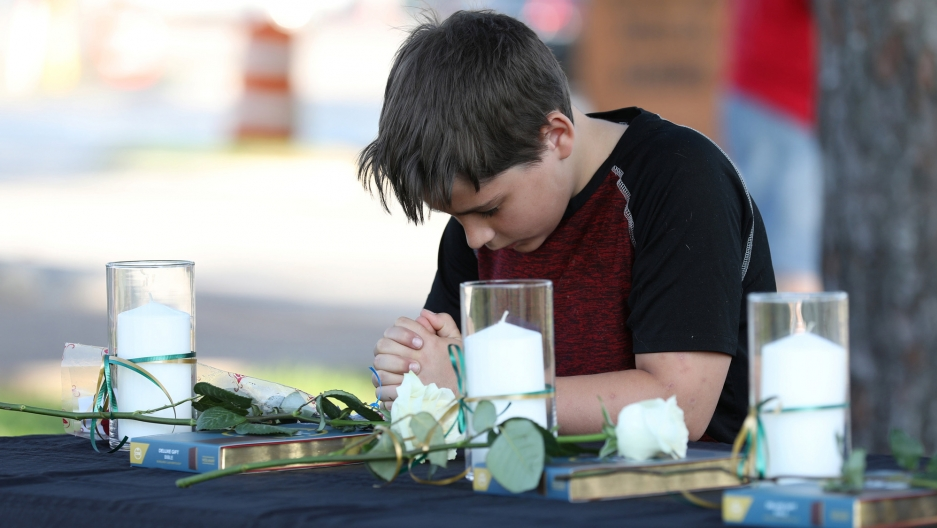 A young boy bends his head in prayer. He is surrounded by several white candles on either side.
