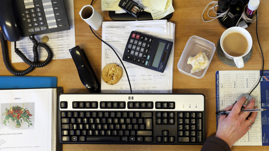 A desk full of food, keyboard, coffee and other stuff.
