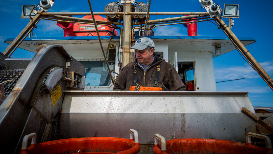 Captain Christopher Brown sorts fish at the F/V Proud Mary's conveyor, with the electronic monitoring cameras visible behind him.