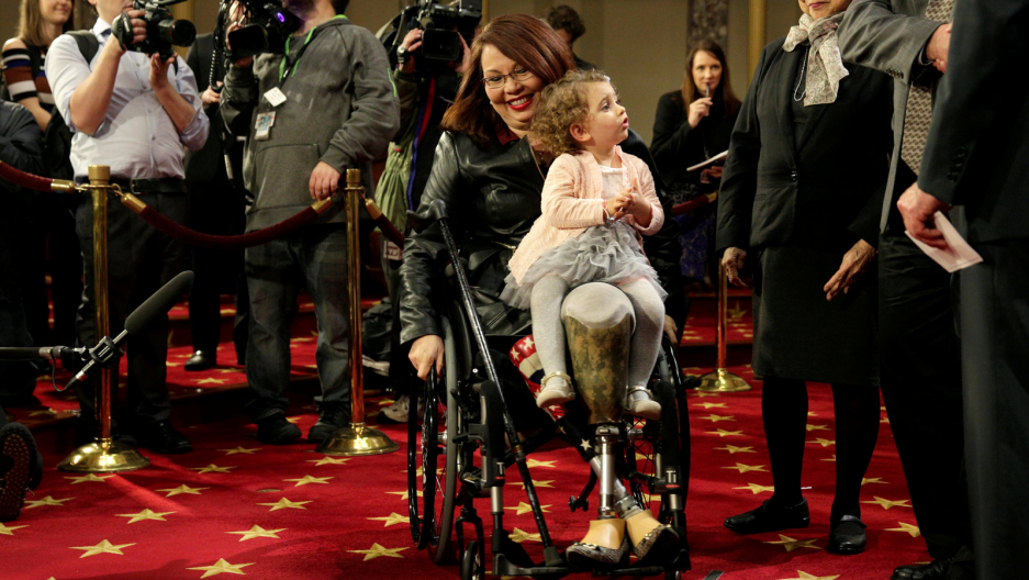 Senator Tammy Duckworth carries her daughter Abigail during a mock swearing-in with US Vice President Joe Biden during the opening day of the 115th Congress on Capitol Hill in Washington, DC, Jan. 3, 2017.