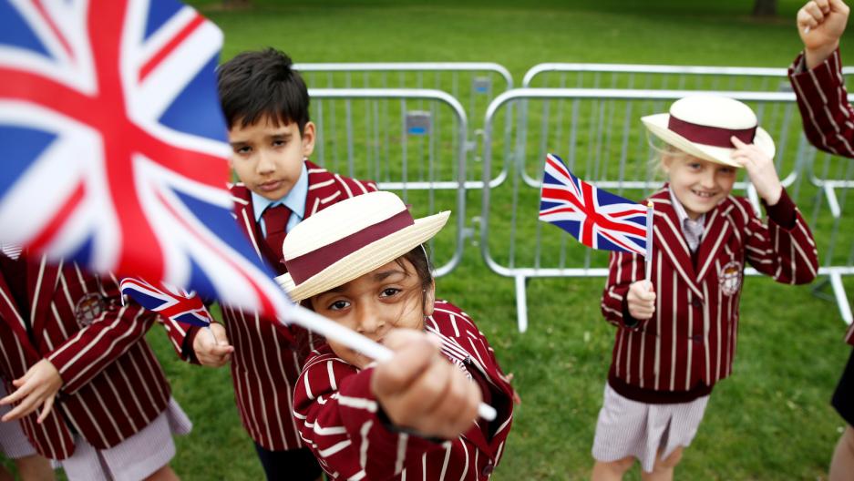 Schoolchildren wave British flags in a garden just days before the next royal wedding.