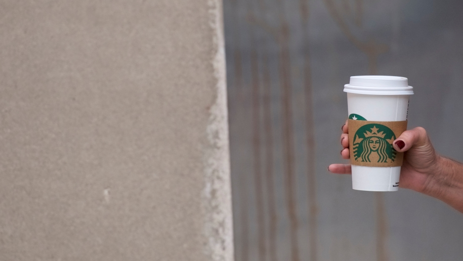 A woman walks through Center City in  Philadelphia, Pennsylvania, clutching a hot Starbucks beverage