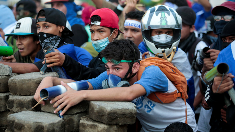 Nicarguan youth sit behind a barricated with homemade mortars as they fight the government.