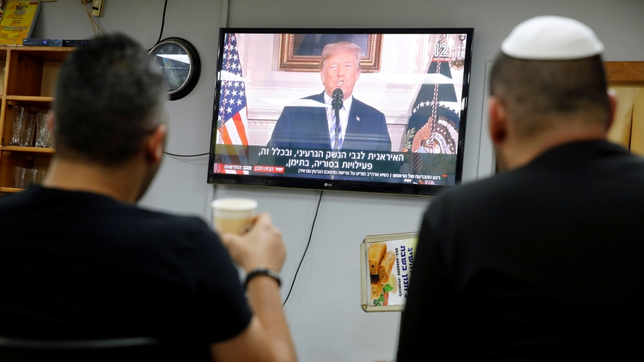 Israelis sit in a coffee shop, watching a television broadcast of US President Donald Trump speaking at the White House, May 8, 2018.