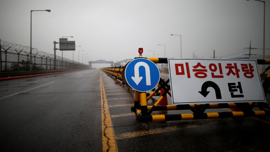 A blue traffic sign with a u-turn symbol is seen on the Grand Unification Bridge.