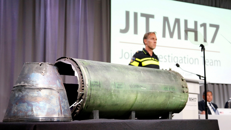A large piece of silver meta, a damaged missile,l sits on a table while MH 17 is projected in the background of a screen.