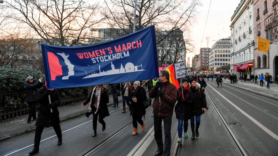 "People carry a large banner that says ""Women's March Stockholm"" down a wide city street."