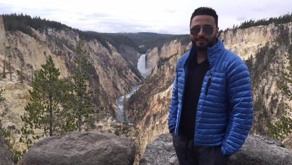 a man standing before a ravine and waterfall in Yellowstone National Park.