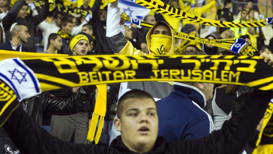 fans in the stands shout slogans during a match