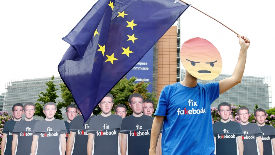 A protester holds an European Union flag next to cardboard cutouts depicting Facebook CEO Mark Zuckerberg during a demonstration ahead of a meeting between Zuckerberg and leaders of the European Parliament in Brussels, Belgium, May 22, 2018.