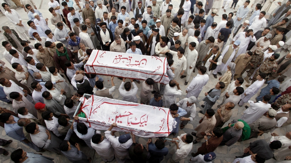 Hazara men carry the coffins of their relatives who were killed after gunmen opened fire on a car, during a funeral ceremony in Quetta, Pakistan, July 19, 2017.