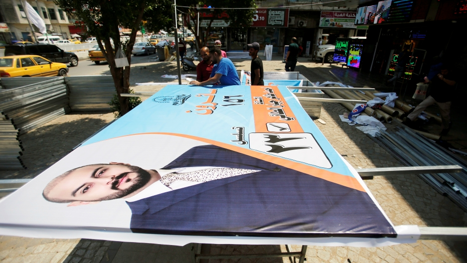 Iraqi men work on the campaign posters of candidates ahead of May's parliamentary election, in Baghdad, Iraq, April 14, 2018.