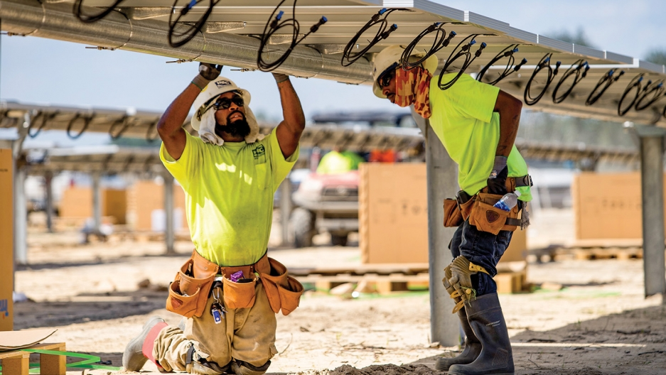 Workers install panels at a solar farm built by Cypress Creek Renewables in Laurinburg, North Carolina. The company has cancelled projects in 10 states since new tariffs were implemented.